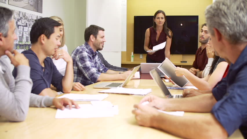 Female boss standing and talking to group of colleagues seated at boardroom table. - HD stock footage clip