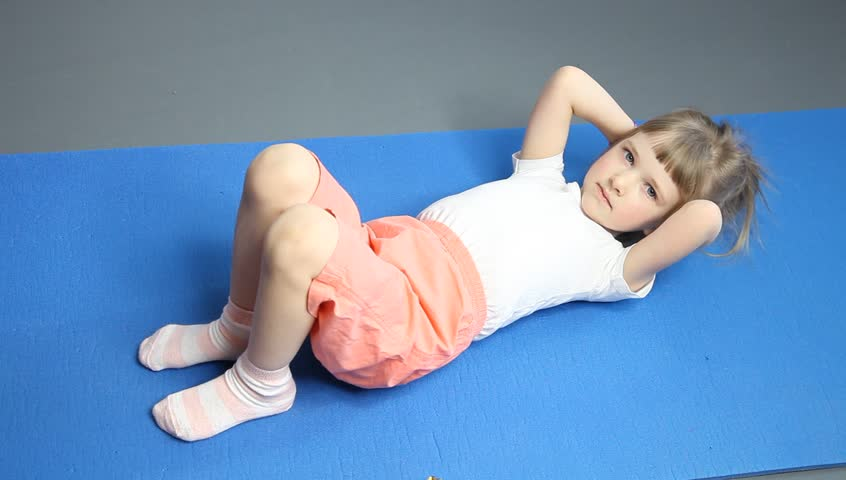 Pretty Little Girl Doing Exercises On A Gymnastic Mat