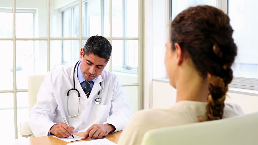 Doctor speaking with his sick patient at desk in the office at the hospital - HD stock footage clip