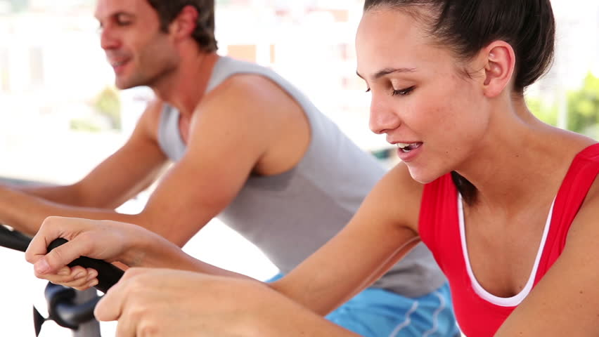 Fit couple working out on exercise bikes at the gym