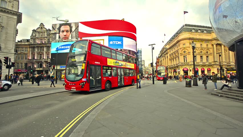 LONDON, UNITED KINGDOM - circa DECEMBER, 2013: Public transportation around Piccadilly circus in circa December, 2013 in London, UK. Red double decker bus passing by, Wide angle lens .