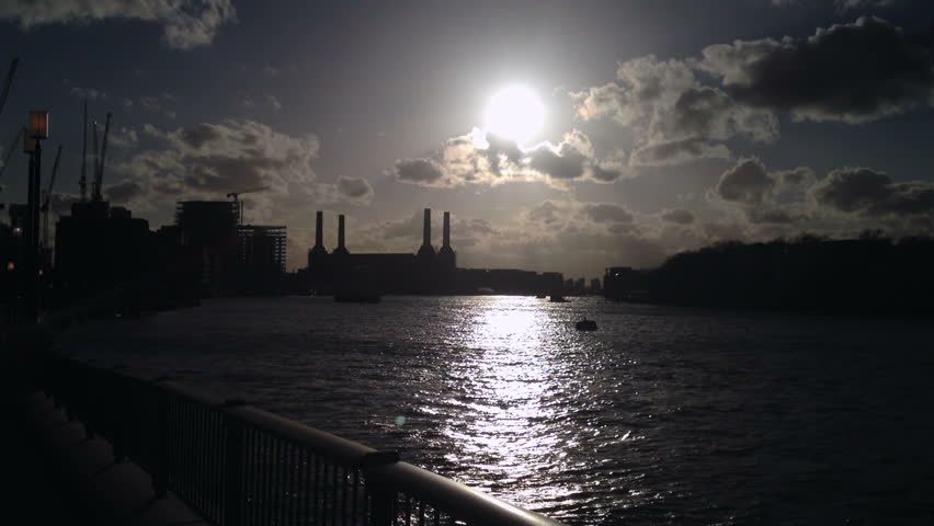 Looking up the river Thames, London towards Chelsea with Battersea Power Station on the left, sunlight glinting on the river and mooring buoys.