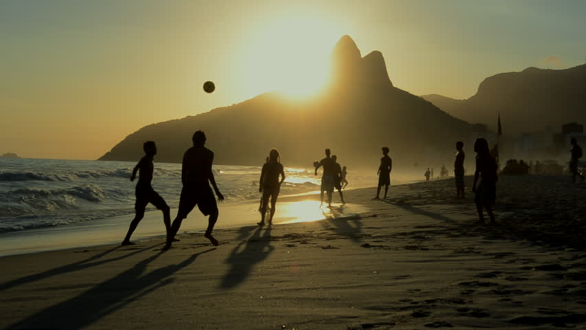 Silhouettes of Carioca Brazilians playing altinho keepy uppy beach football at sunset on Ipanema Beach Rio de Janeiro Brazil