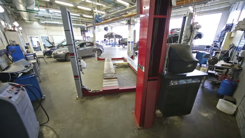 Cars and equipment for wheel alignment camber in workshop - HD stock video clip