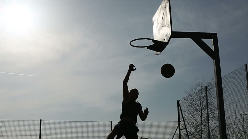 Basketball player silhouette making a fancy 180 degree slam dunk - HD stock video clip