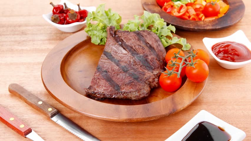 Fresh rich juicy grilled beef meat steak fillet with marks on wooden plate over table decorated with lettuce salad and cutlery new york styled cuisine 1920x1080 intro motion slow hidef hd | Shutterstock HD Video #5994638