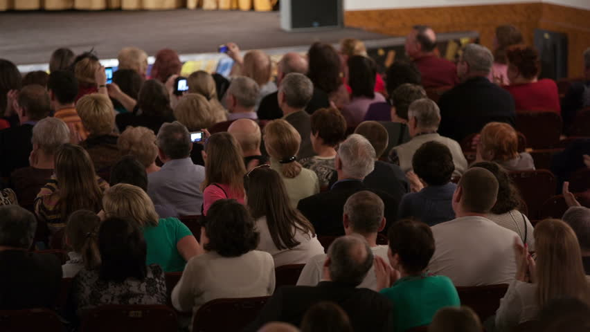 Grateful audience applauding and taking pictures. View from the back of a packed auditorium or theatre with people seated in an audience watching a live performance on a stage