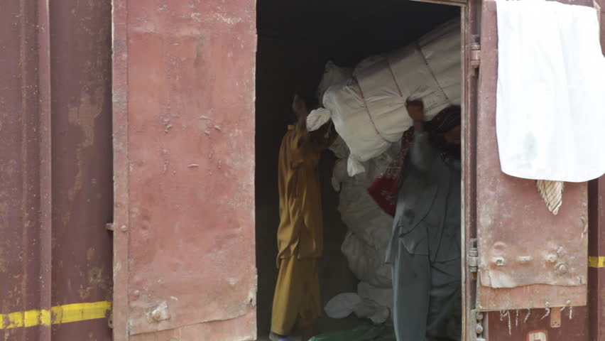 LAHORE, PAKISTAN - JULY 25, 2013: Workers ubnload bags of freight manually from a rusted, antiquated Pakistan Railway freight car into a shed. - HD stock footage clip