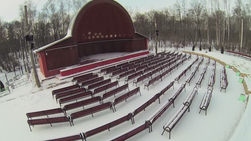 rows of benches near small stage with round roof in winter