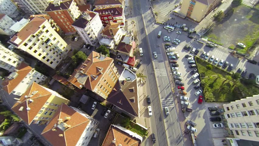 Overhead right pan across roofs, houses and cars along suburban street. Flying over right pan across houses along suburban architecture.