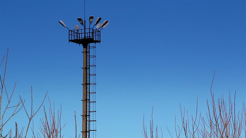 The top view of the prison tower with large lights on it and the metal wire fence on the side - HD stock footage clip