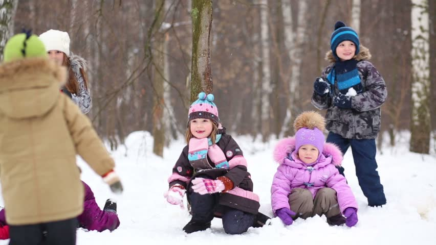Five children throw snowballs in winter park with snow and trees - HD stock footage clip