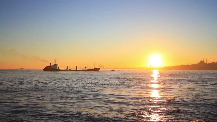 Cargo ship cruising on sunset. Cargo ship with deck cranes sailing into Marmara Sea towards Istanbul.