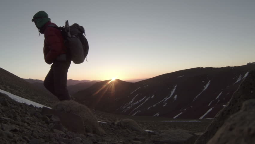 Silhouetted mountain climber at sunrise, in the High Atlas Mountains of Morocco.