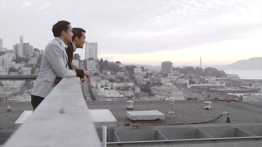 Two guys just hanging out on a roof and looking out to San Francisco bay during the day
