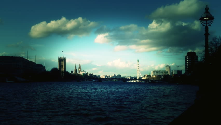 The Thames River in London at dusk from the south bank looking across and downstream to the houses of parliament, Victoria Tower and Big Ben Clock Tower.