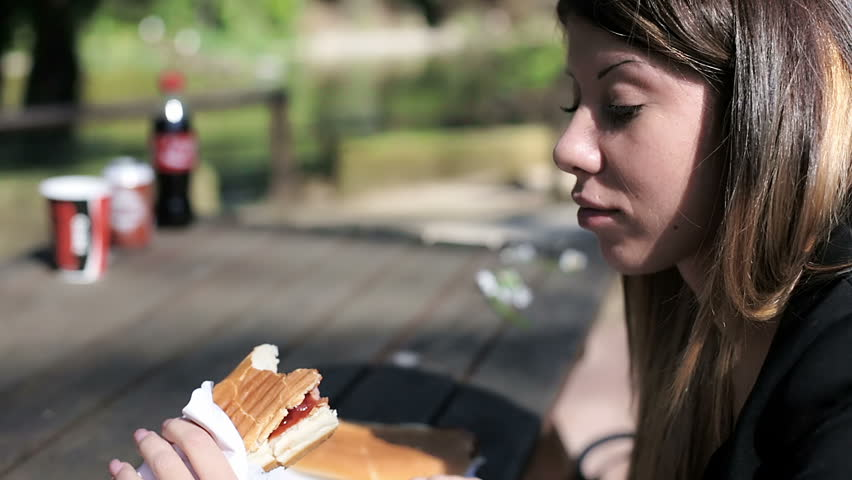 Beautiful young woman eating a hot dog in a park | Shutterstock HD Video #6091190