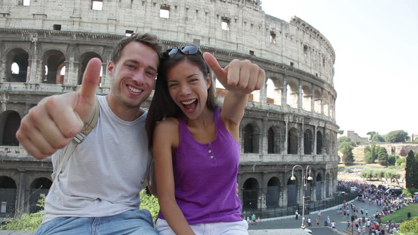 Travel couple happy thumbs up by Colosseum, Rome, Italy. Smiling young romantic couple traveling in Europe looking at camera smiling in front of Coliseum. Caucasian man and Asian woman.