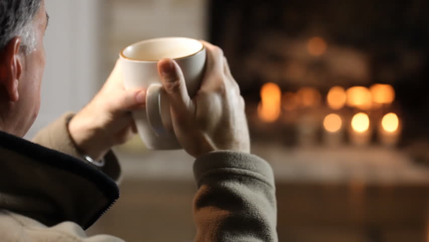 Close up of man drinking coffee in front of a fireplace. - HD stock video clip