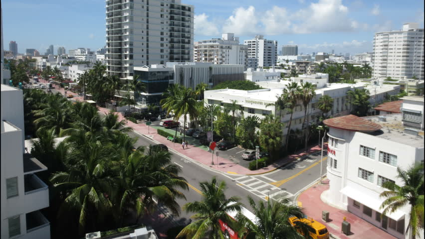 MIAMI BEACH - APR 2014: The city of Miami Beach, Florida. Overlooking Collins Avenue on a sunny day, shot in time lapse and tilting up. - 4K stock video clip
