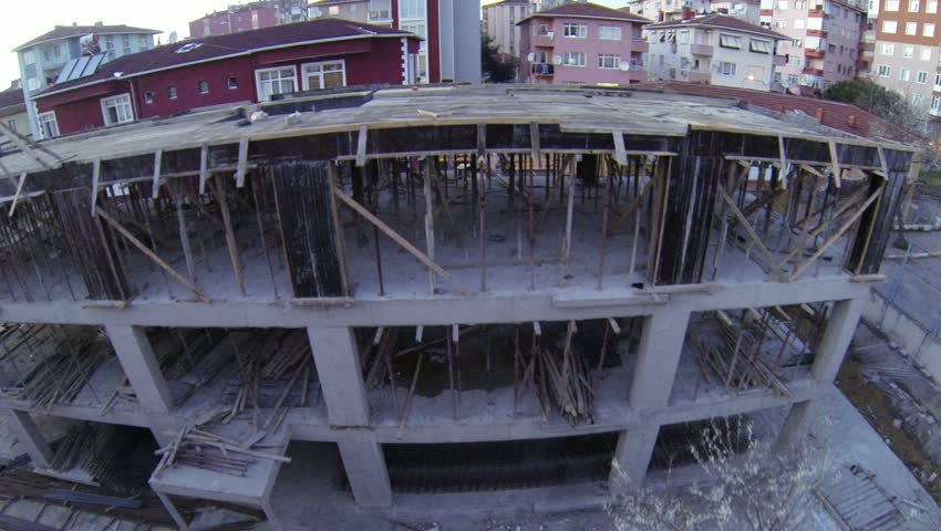 Low-flying over construction block in late afternoon. Aerial video of building construction from flying camera.