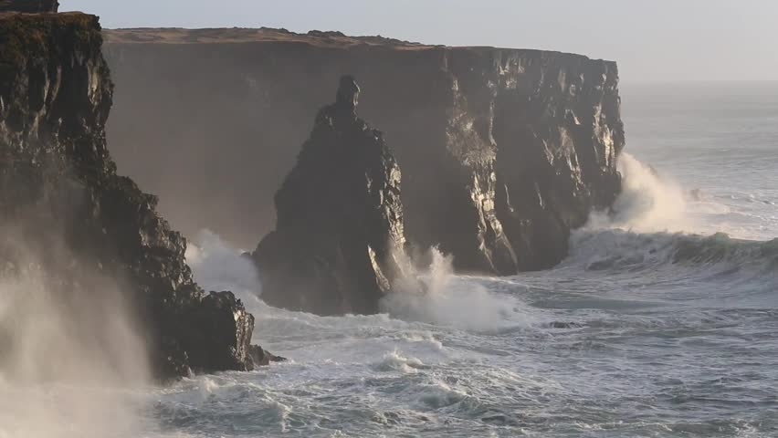 Powerful ocean waves crashing on the rocks in the western part of Iceland in the sunset light