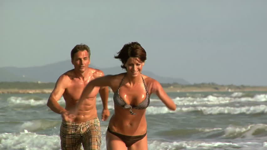 Happy woman running on the beach with a man - HD stock footage clip