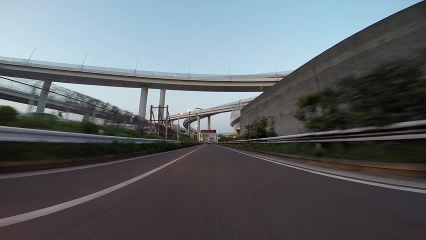 (Driver POV) Twilight drive wide view of Tokyo Bay Area. Departure from Daikoku Futo.