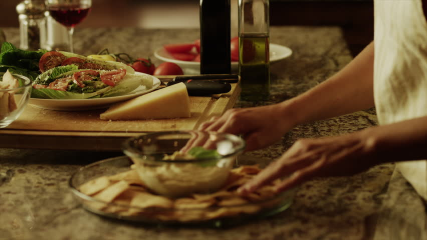 Close up panning shot of woman carrying salad and appetizer in kitchen / Cedar Hills, Utah, United States - HD stock footage clip
