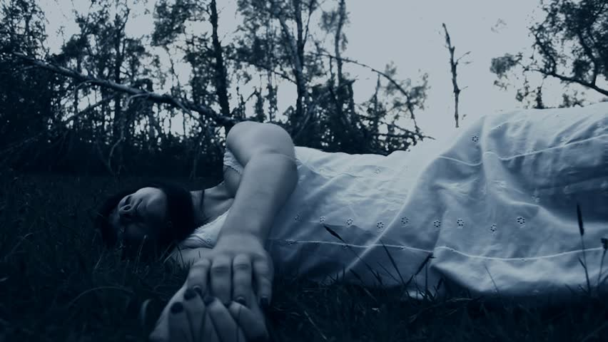 Horror scene - footage of a unconscious woman lying in the grass