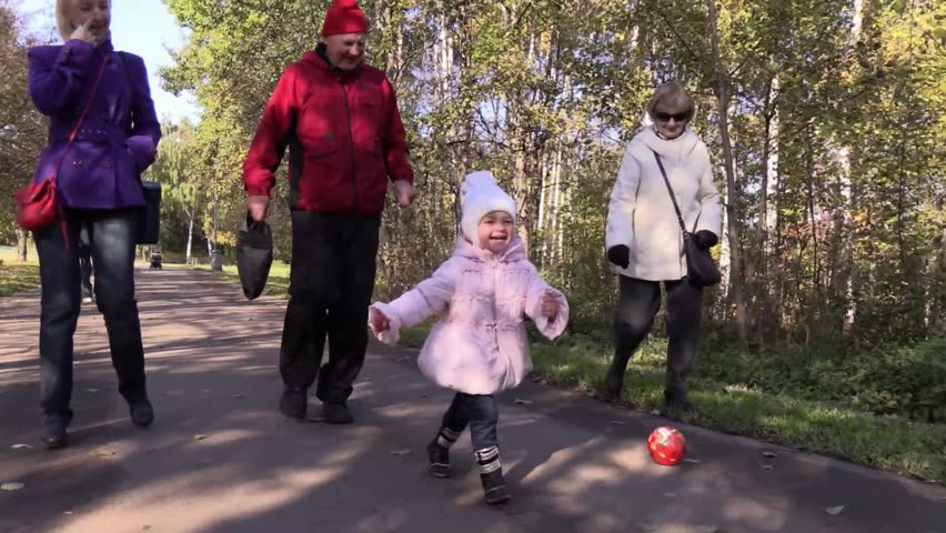 Cheerful girl runs on a background of happy family on camera in sunny autumn park. Steady Fly Cam. Slow Motion. - HD stock footage clip