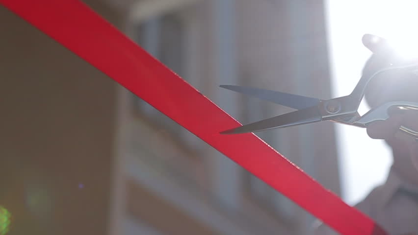 Cutting a red ribbon with scissors. Grand opening