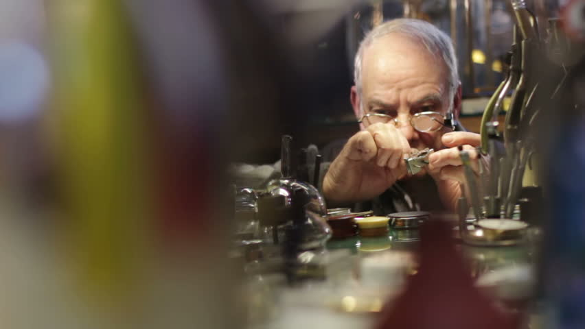 Watchmaker checks the operation of a old clock
