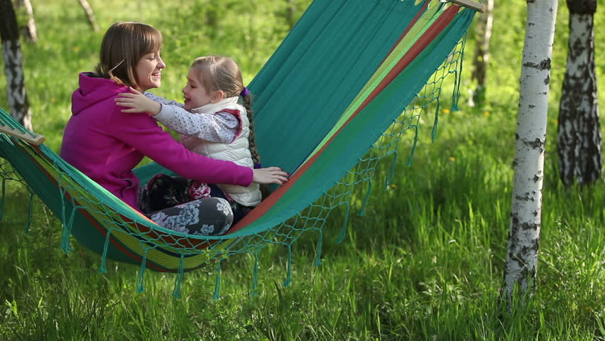 Happy mother and daughter hugging and sitting in a hammock outdoor - HD stock footage clip