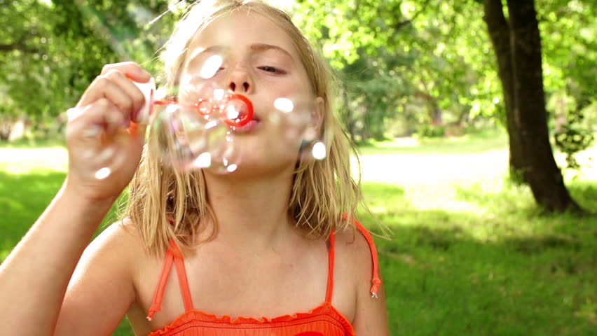 Girl in park blowing bubbles with bubble wand in slow motion | Shutterstock HD Video #6208208