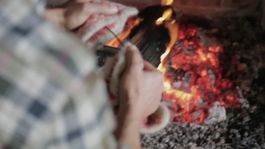 Man removing metal pot with pasta from fireplace - HD stock footage clip