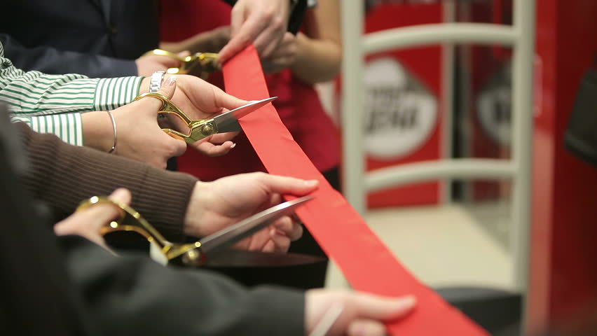 New store opening. Ceremonial red ribbon cutting. Scissors in hands.