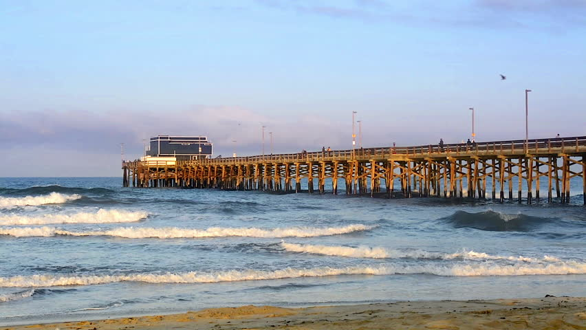 Balboa pier in Newport Beach, California during sunrise shows a beautiful orange light bouncing off the pier and waves moving towards shore. | Shutterstock HD Video #6306083