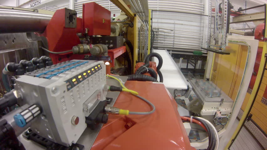 Time lapse with a wide-angle, point-of-view GoPro shot from a robotic arm in a factory, as it grabs plastic products from an injection molding machine and carries them to a machine to apply a label. POV.