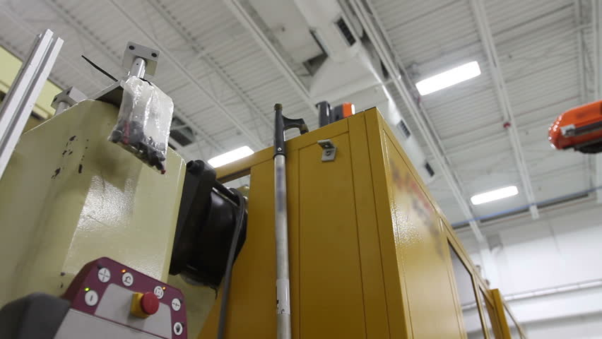 Camera follows the movement of a robotic arm in a factory as it carries a product to the conveyor belt, then picks up a label for the next product