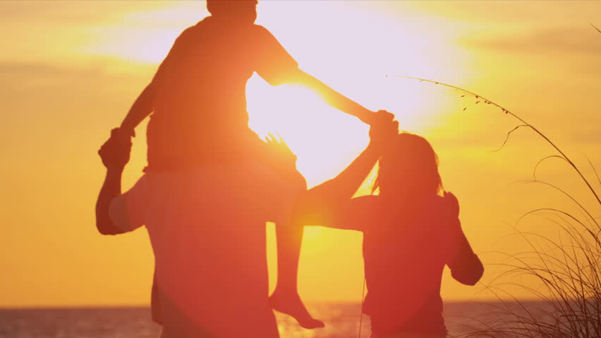 Ethnic Family Vacation Sunset Beach - Young boy on fathers shoulders as family in silhouette stand on beach watching sunset slow motion shot on RED EPIC
