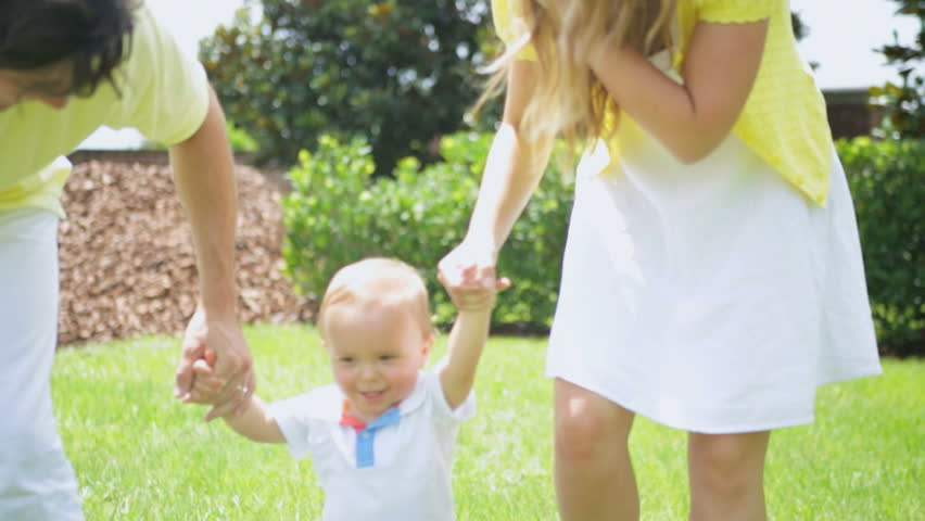 Parents Helping Little Boy Practice Walking Barefoot Park - Healthy happy young male Caucasian child practicing walking grass outdoors park holding parents hands - HD stock video clip