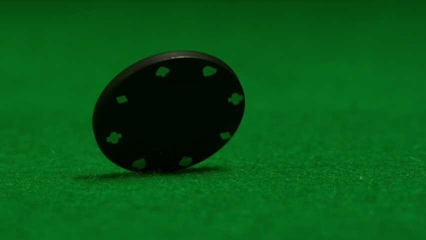 Black chip spinning on casino table in slow motion