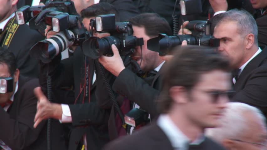 """CANNES, FRANCE - MAY 2014: Photographers gesturing along the red carpet at the premiere of """"Mr. Turner"""" at 67th Cannes Film Festival."""
