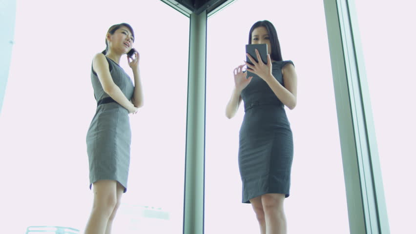 Ambitious young female Asian Chinese stock brokers using smart phone mini tablet technology modern skyscraper building shot on RED EPIC | Shutterstock HD Video #6374276