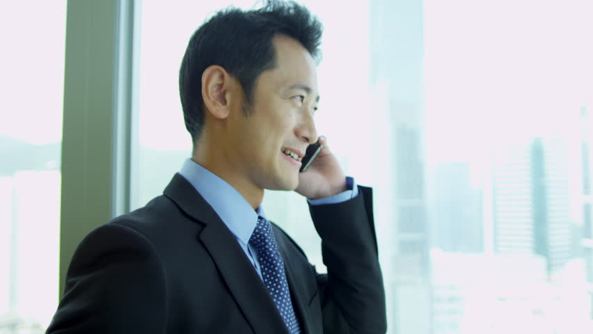Successful young Asian Chinese businessman talking smart phone window modern office building head shoulders portrait shot on RED EPIC