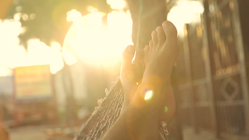 Feet swinging in a hammock, POV. Relaxing on the beach at sunset with flare.