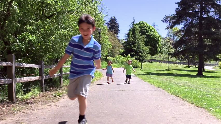 Three Excited Asian Kids Run Down Path, Toward Camera. Asian family playing outdoors.  - HD stock video clip