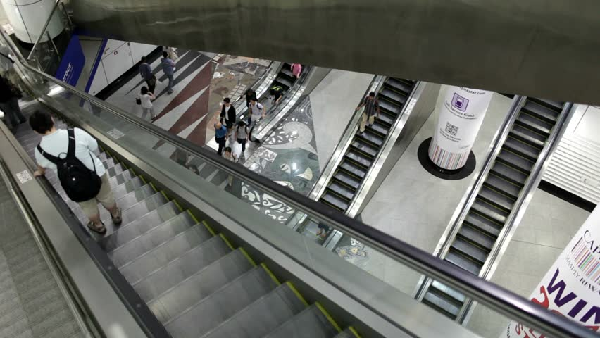 Commuters on escalators, at Singapore metro station. - HD stock video clip