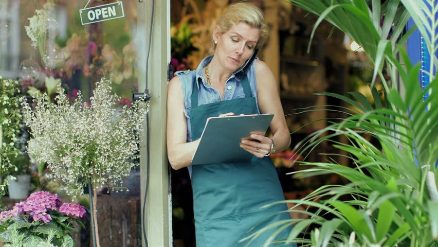 A Florist speaks on the phone, jotting notes eagerly as she leans against the doorway of her shop
